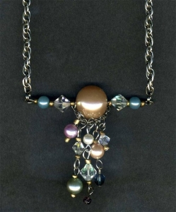 Necklace on chain with large faux pearl bead and faux pearl and crystal dangles.