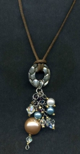 Necklace on cord with silver color disc and faux pearl and crystal dangles.