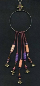 Necklace with large ring, bells, and purple and peach beads.