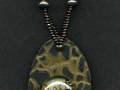 Necklace with gold and black oval pendant with glass.