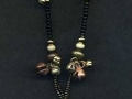 Necklace with lime green and black circular pendant with bells and glass.