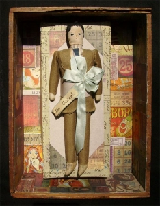 Antique doll displayed in shadow box made of a Necco Wafer box that looks like it's probably from the 1930s. It has carnival imagery on the outside, so I decoupaged carnival imagery on the inside and built a hollow box for displaying the doll. There is a band of archival paper holding the doll onto the box.