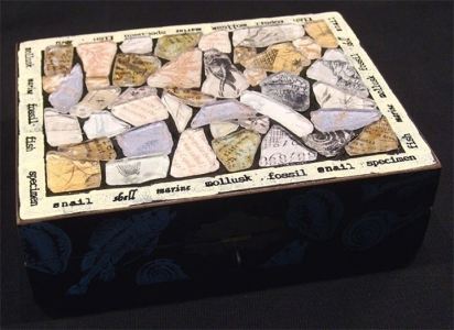 This box was decorated on top with faux beach glass pieces backed with decorative paper. I added some rubber stamping around the sides and the lid border. The source of the box was a thrift store.