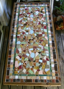 Here is a mosaic table using salvaged tiles and ones that I made. My garden soil has a lot of construction debris in it - I dug up quite a few of these tiles! My Dad built the table for me out of scrap wood.