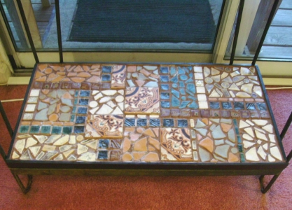Mosaic shelf made to go on the bottom level of an aquarium stand. Most of the tiles are handmade by me, there are a few salvaged ones in there.